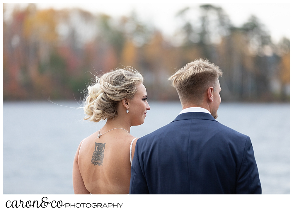 a bride and groom looking out over Rangeley Lake, Rangley Maine wedding