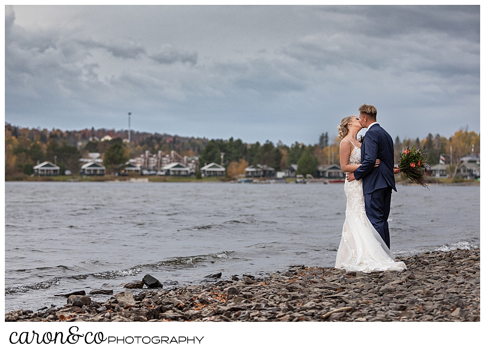 a bride and groom kiss while standing on the shore of Rangeley Lake, Rangeley Maine