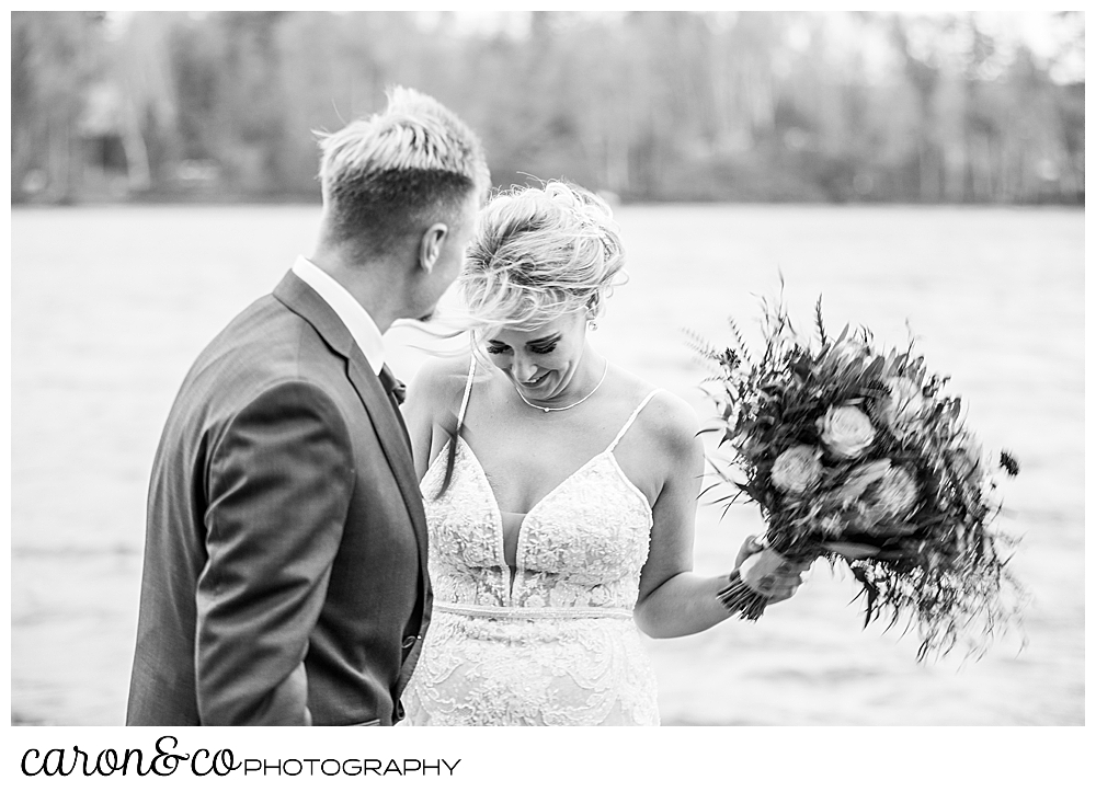 black and white photo of a bride and groom standing on the shores of Rangeley Lake, during a Rangeley Maine wedding