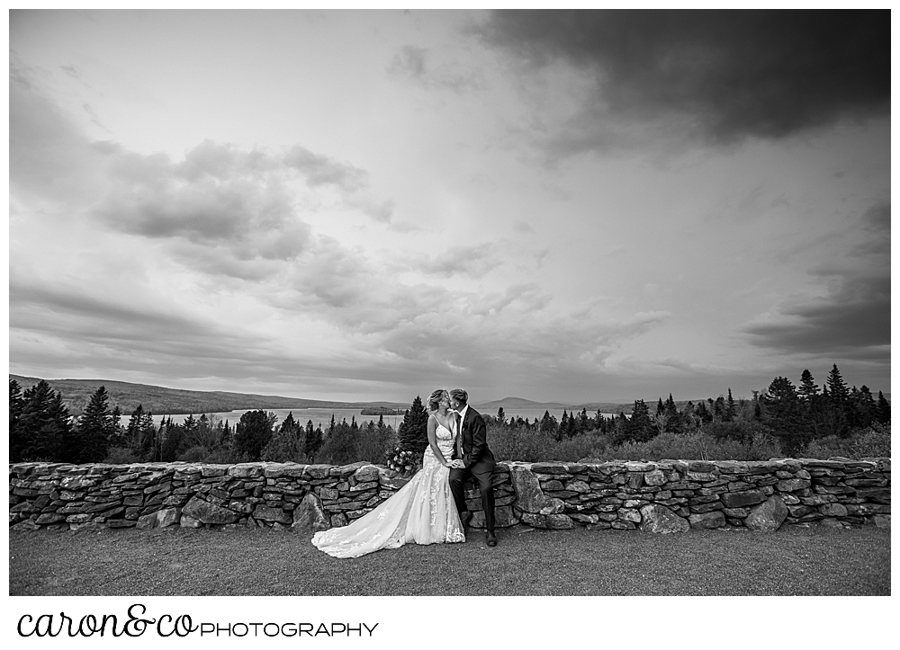black and white photo of a bride and groom sitting on a stone wall with a dramatic view and skies in the background during their Rangeley Maine wedding