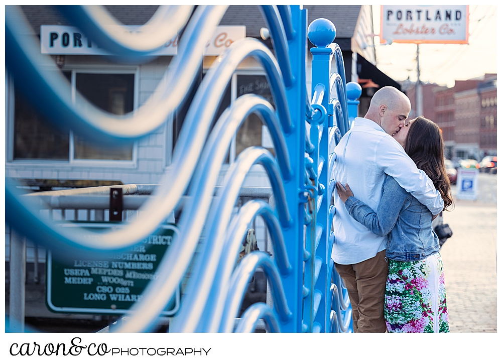 man and woman kissing by the wave wall during a Portland Maine spring engagement session