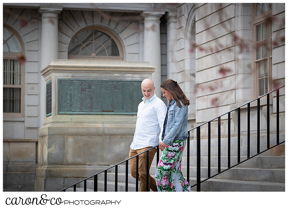 man and woman holding hands walking down the steps of the Portland Maine City Hall, during a Portland Maine spring engagement photo session