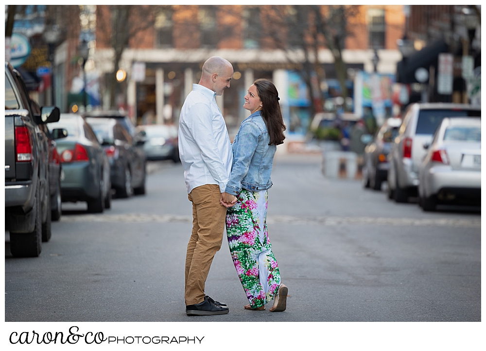 a man and woman in the middle of Exchange Street, Portland, Maine, during a Portland Maine spring engagement photo shoot