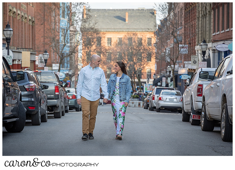 a man and woman holding hands walk up the middle of Exchange Street, Portland, Maine, during their Portland Maine spring engagement photo shoot