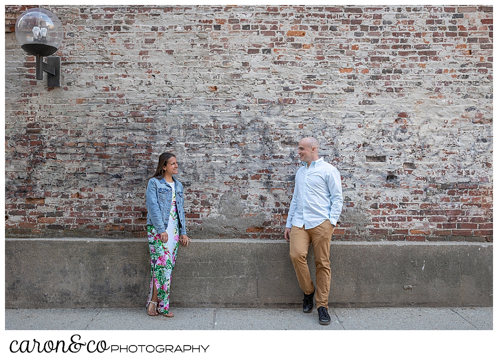 a man and woman standing in front of a brick wall in Portland, Maine, during a Portland Maine engagement session
