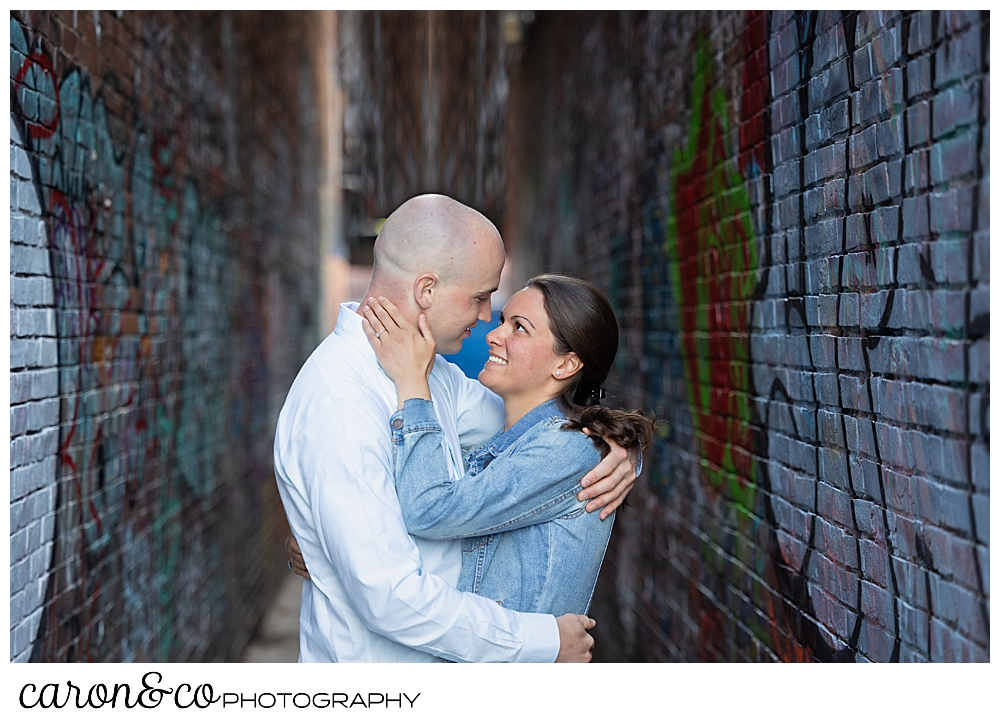 a man and woman hug in an alley way in the Old Port, Portland, Maine, during their Portland Maine engagement session