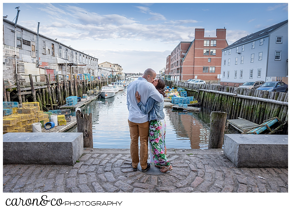 a mand and woman stand with their backs to the camera, kissing, in a walkway between two piers in Portland, Maine, during their Portland Maine spring engagement photo session