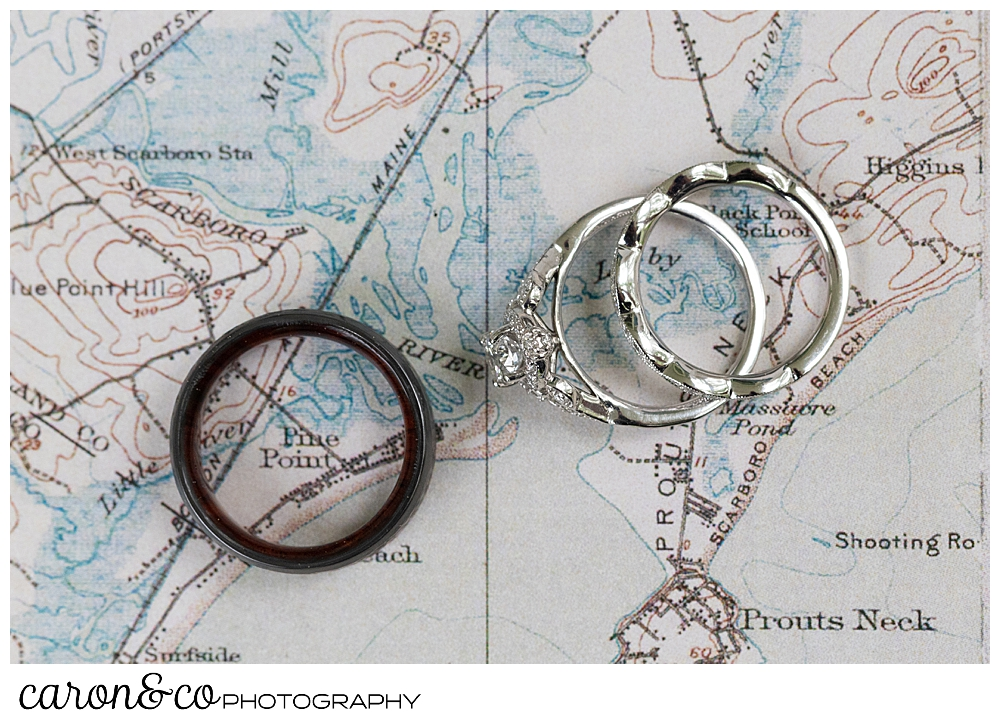 wedding bands and engagement ring on a background of a Maine map, the man's ring is encircling Pine Point Maine wedding