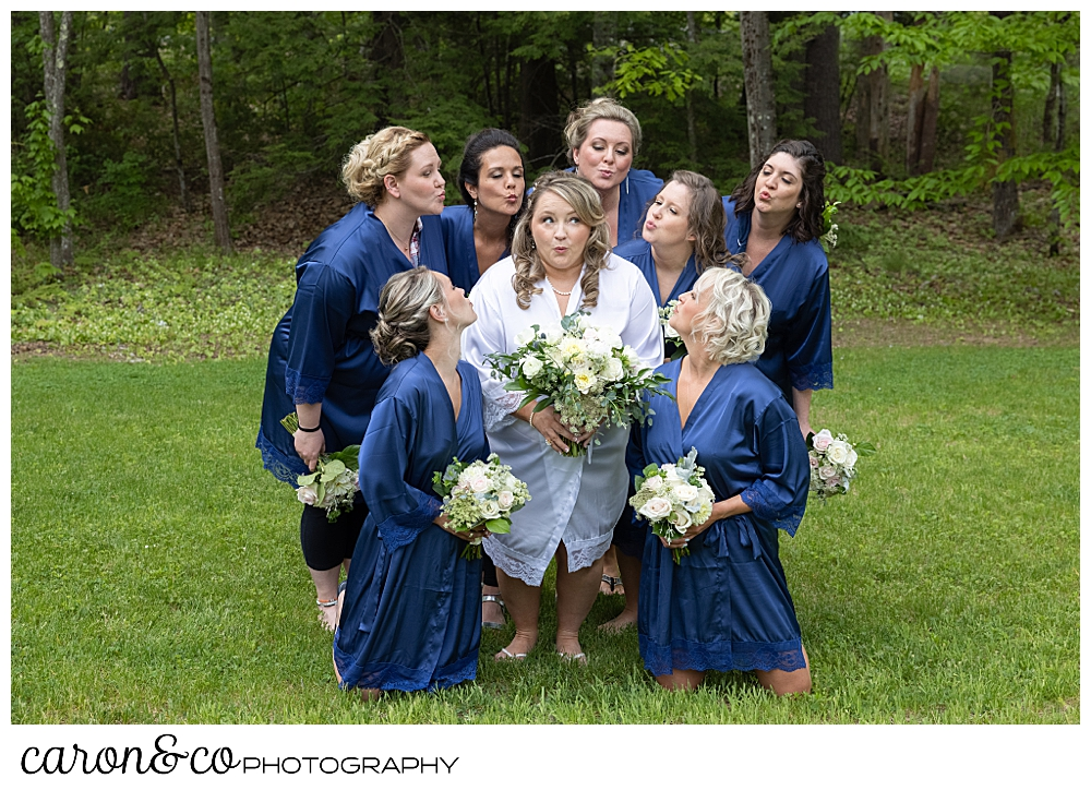 bride in a white robe, surrounded by bridesmaids in blue robes, blowing kisses