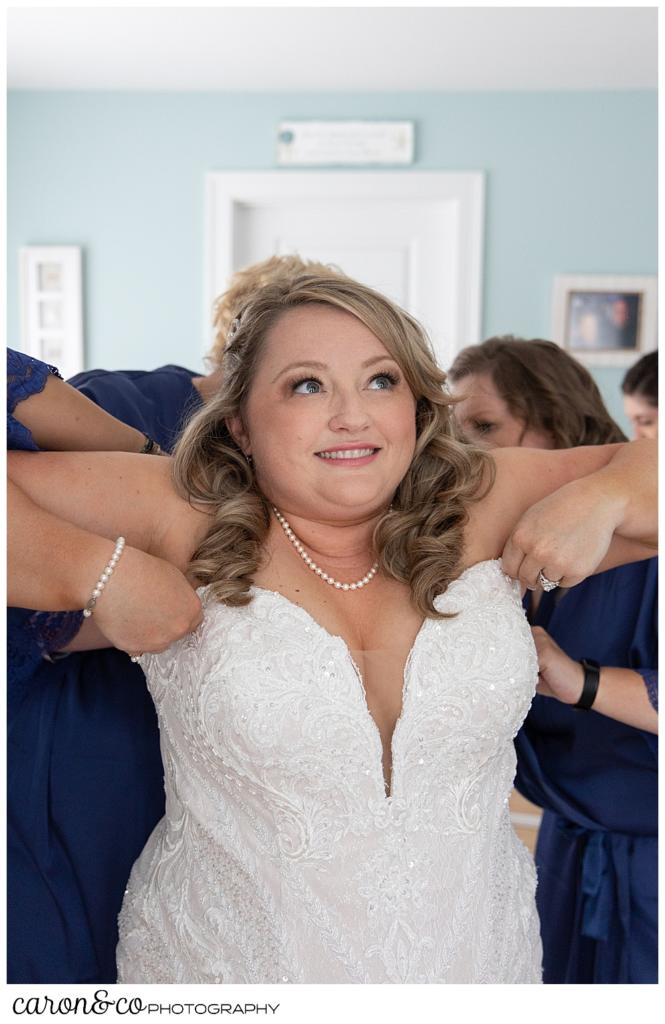 a smiling bride holds up her wedding dress while bridesmaids in blue button the back of her dress