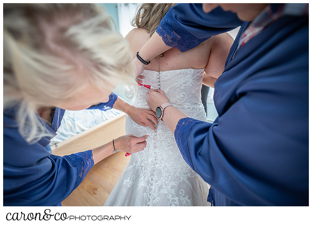 bridesmaids in blue, buttons up the back of a bride's wedding dress