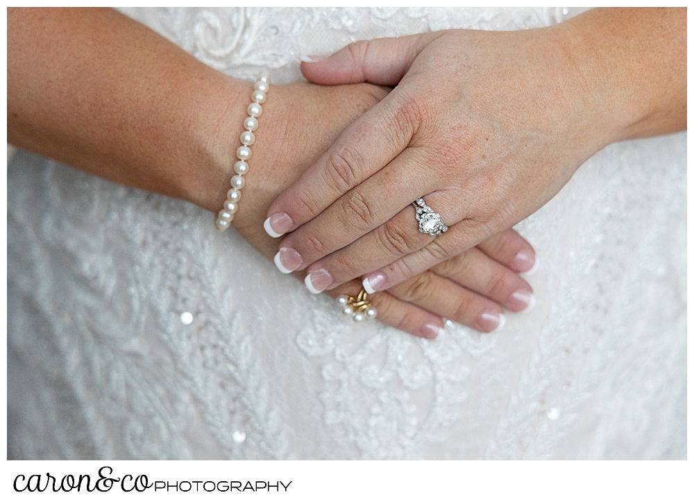 a bride's hands, clasped in front of her, she's wearing a diamond engagement ring, and a pearl bracelet