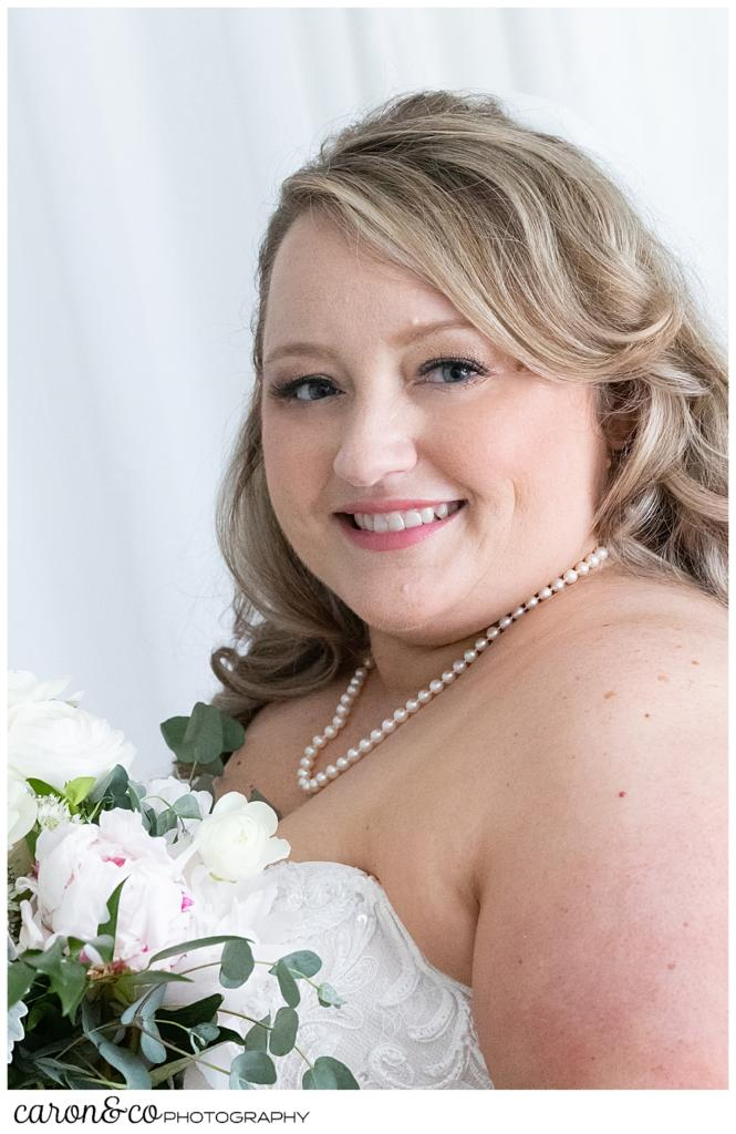 a beautiful bride smiles in her bridal portrait, she is wearing a strapless dress, a pearl necklace, and has white and blush flowers in her bouquet