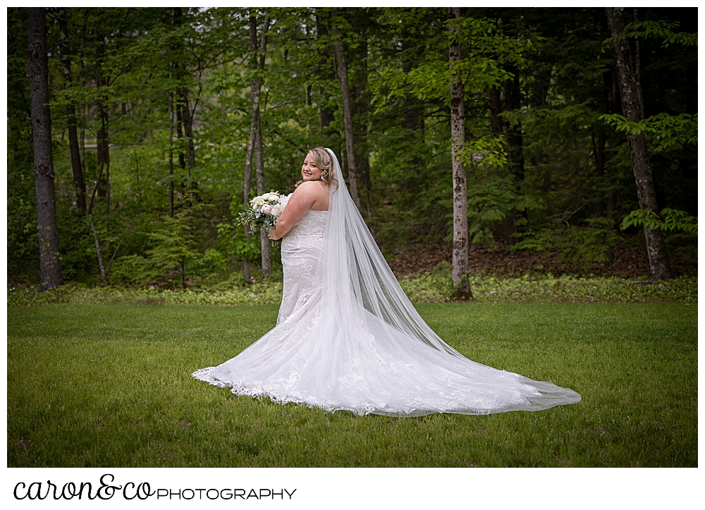 a full length portrait of a bride wearing a white strapless bridal gown, and a chapel length veil, stands in her back yard