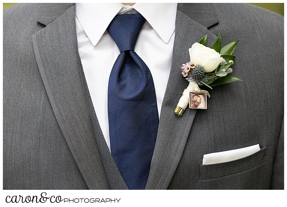 groom details, a gray suit, a white pocket square and shirt, a navy tie, and a white and green boutonniere