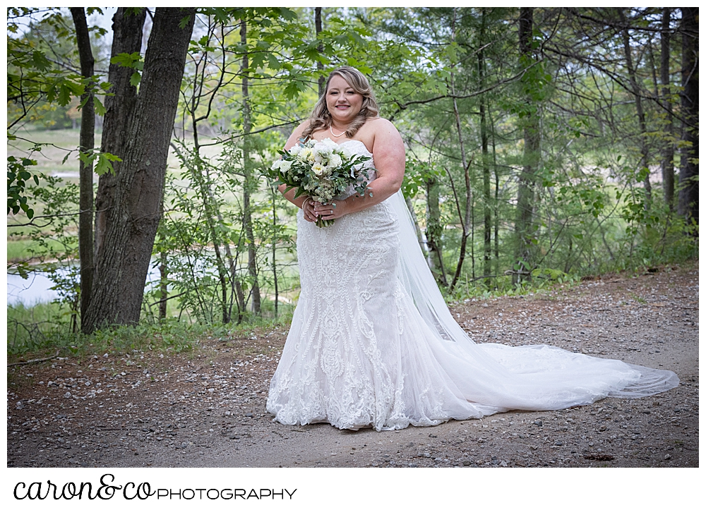 a bride stands on a trail in the woods, she's wearing a strapless white wedding dress and veil, and carrying a bouquet of white, blush and green