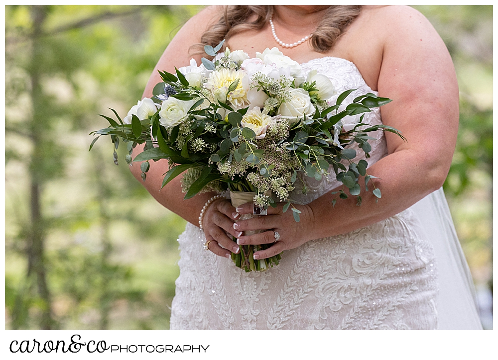 bride holding a beautiful bouquet of white, blush, yellow, and green