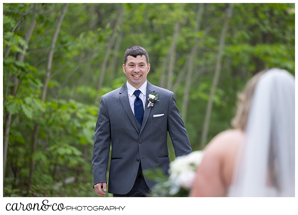 a groom wearing a gray suit, walks towards his bride, smiling broadly