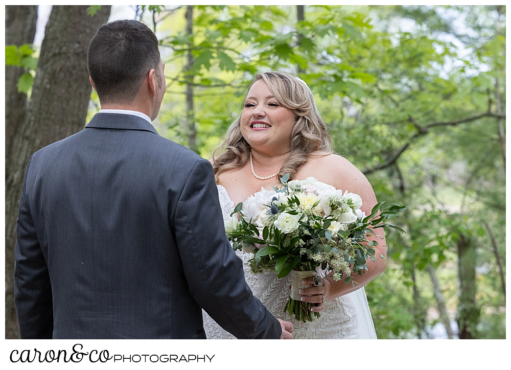 a bride wearing a strapless white dress, holding a bouquet of flowers, smiles as her groom approaches during a wedding day first look