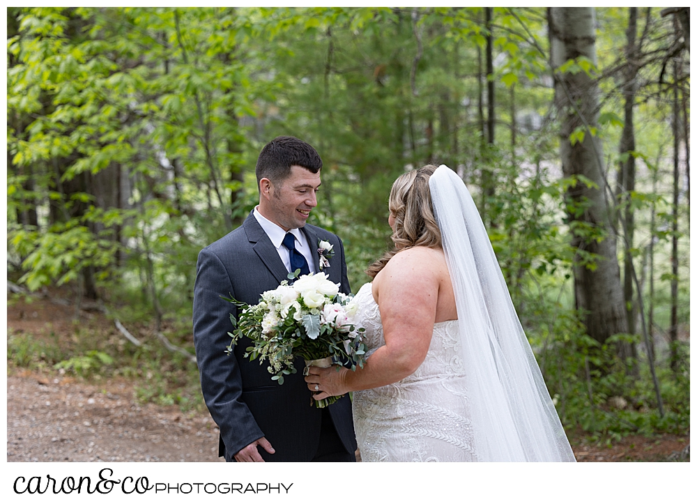 a bride in white, and a groom in gray, stand face to face during a Pine Point Wedding first look