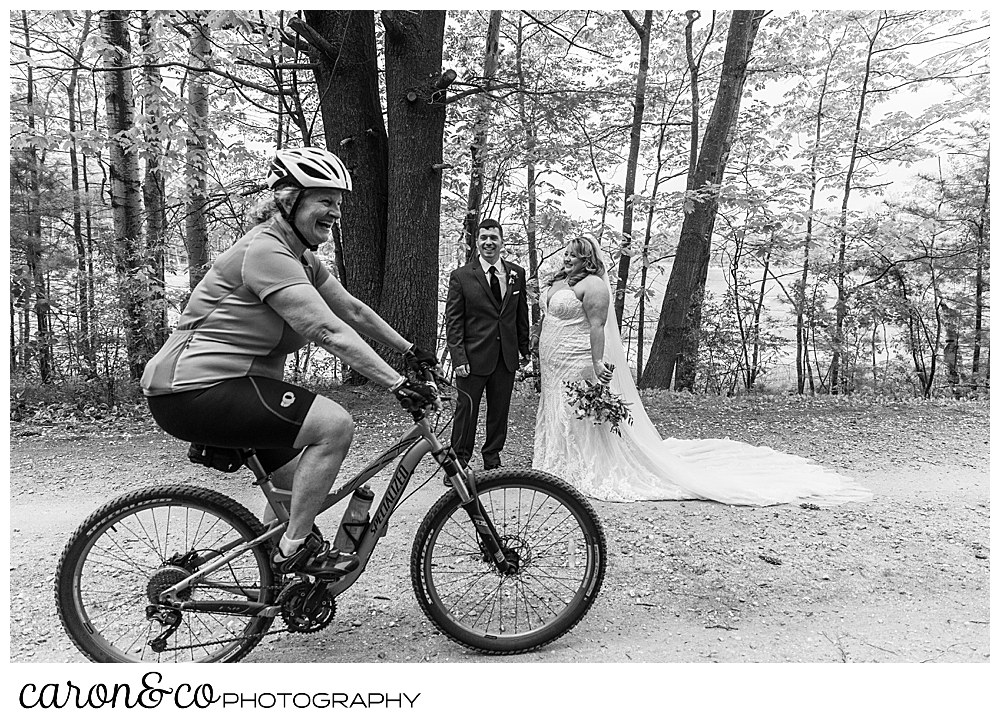 black and white photo of a bride and groom standing together on a path in the woods, as a cyclist goes by in the foreground