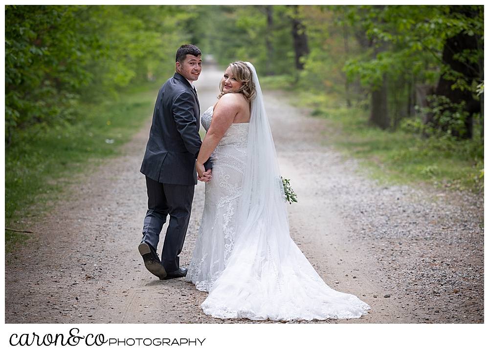 a bride and groom walking on a wooded path, turn to look at the camera