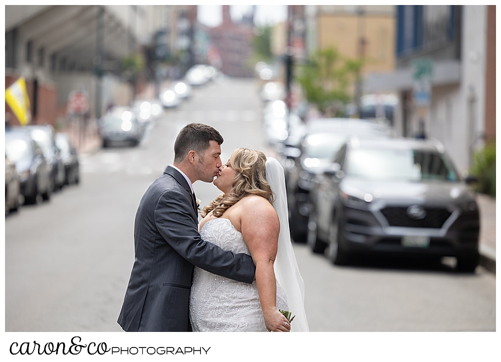 a bride and groom kiss in the middle of downtown Portland, Maine