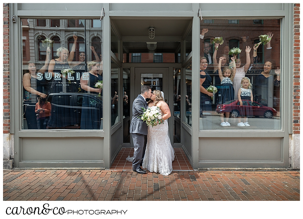a bride and groom kiss in front of Sur Lie Restaurant in Portland, Maine, while their bridal party cheers from inside