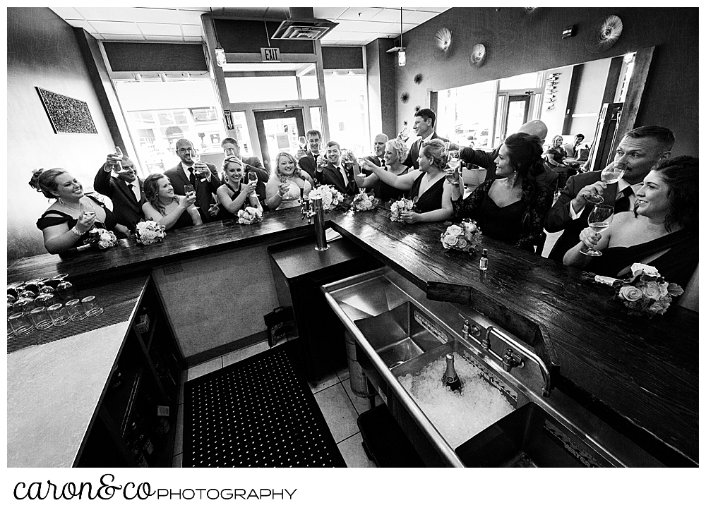 a black and white photo of a bride and groom, with their 16 person bridal party, toasting with Champagne at Sur Lie restaurant in Portland, Maine