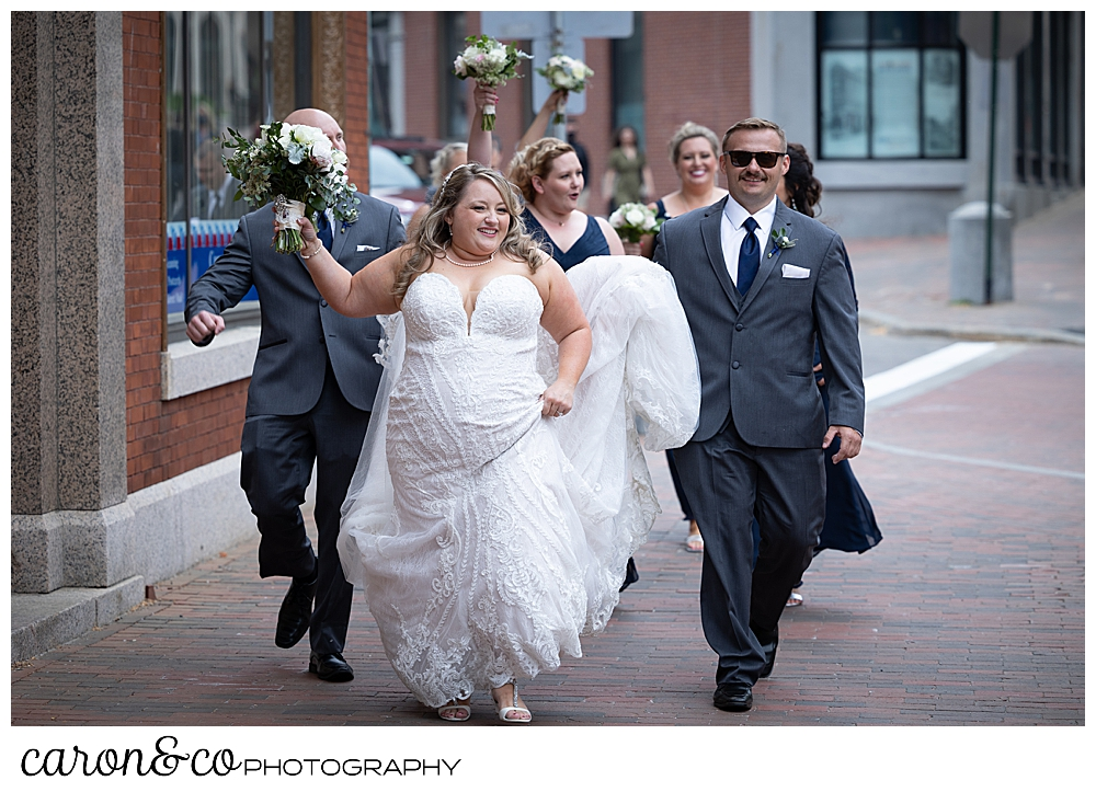 a bride in white, holding a bridal bouquet, walks down the street in Portland, Maine, with her bridal party