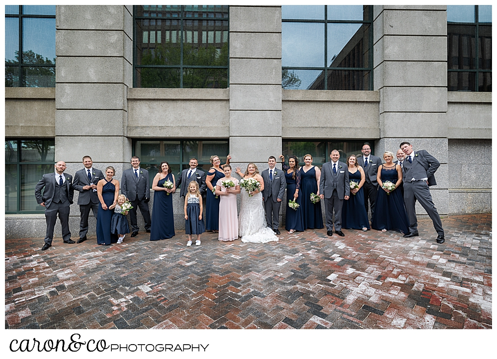 a bride and groom with their bridal party, pose in front of a building in the Old Port, Portland, Maine
