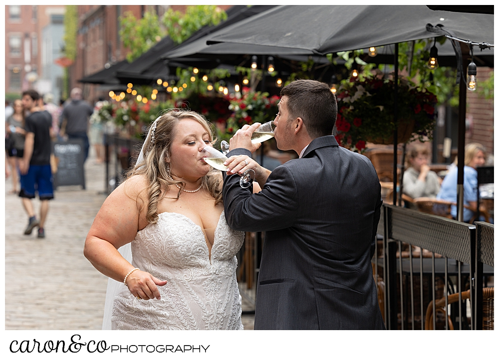 a bride and groom toast each other with champagne, on Wharf Street, Old Port, Portland, Maine