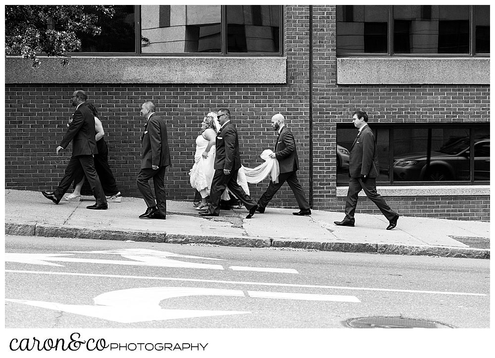 a black and white photo of a Bride and groom with their bridal party, walking along the sidewalk in Portland, Maine