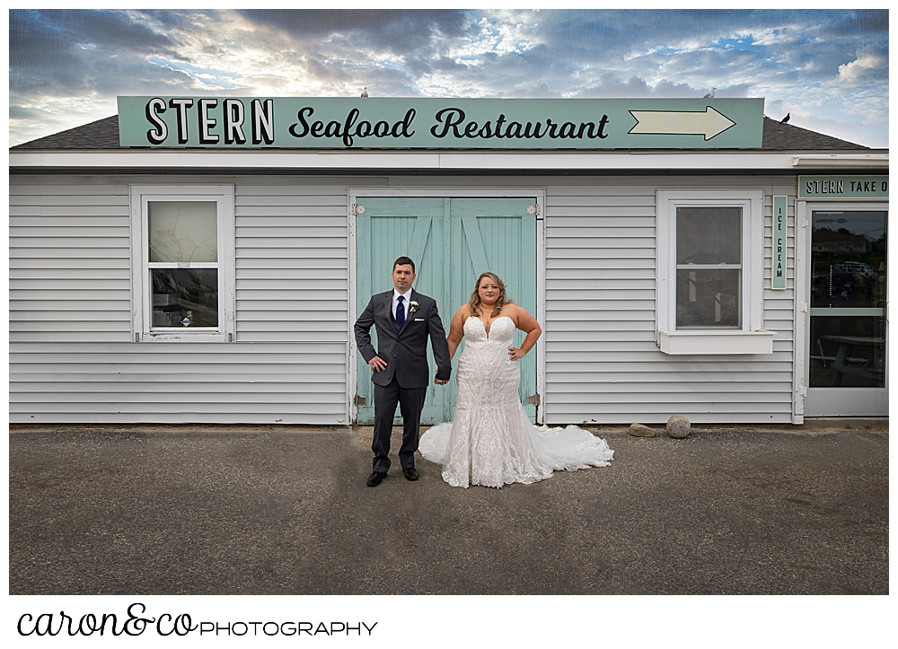 a bride and groom stand together in front of the Stern Seafood Restaurant, Pine Point, Scarborough, Maine