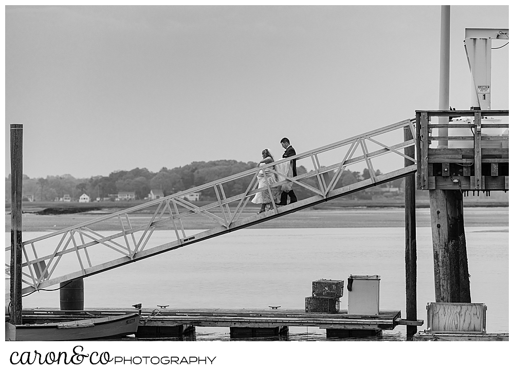 a black and white photo of a bride and groom walking down a ramp during a Pine Point Maine wedding