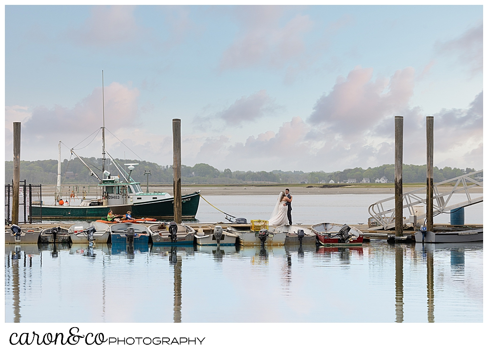 a bride and groom kiss on the docks, with boats and kayaks in the background, at their Pine Point Maine wedding