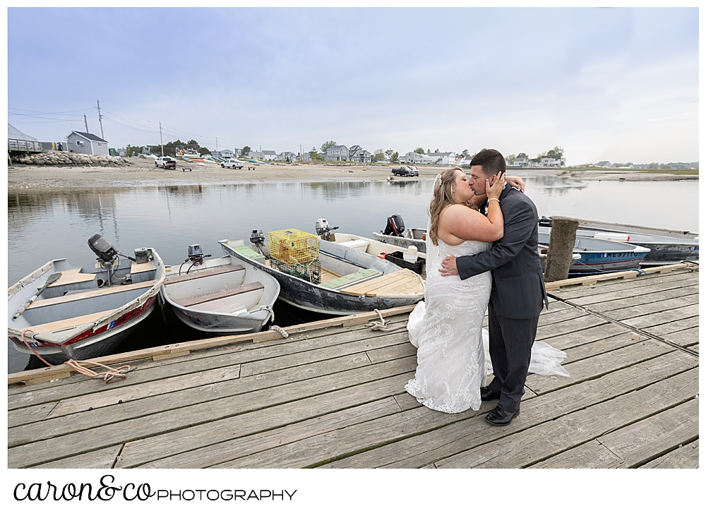 a bride and groom kissing on a fishing dock, at Pine Point, Scarborough, Maine