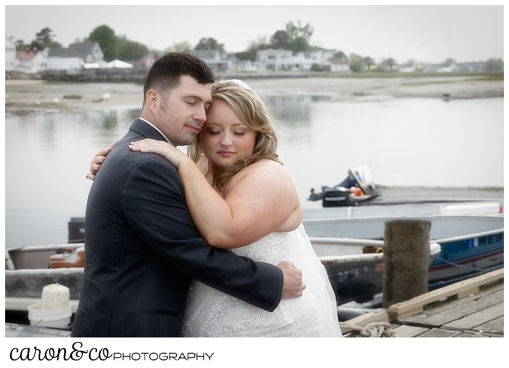 a bride and groom stand cheek to cheek on the dock at their Pine Point Maine wedding