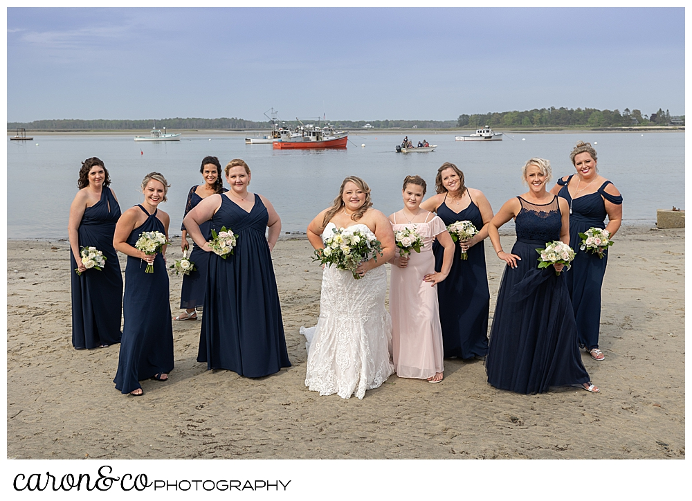 a bride in white, with her bridesmaids in blue, standing on the beach at Pine Point, Scarborough, Maine weddings