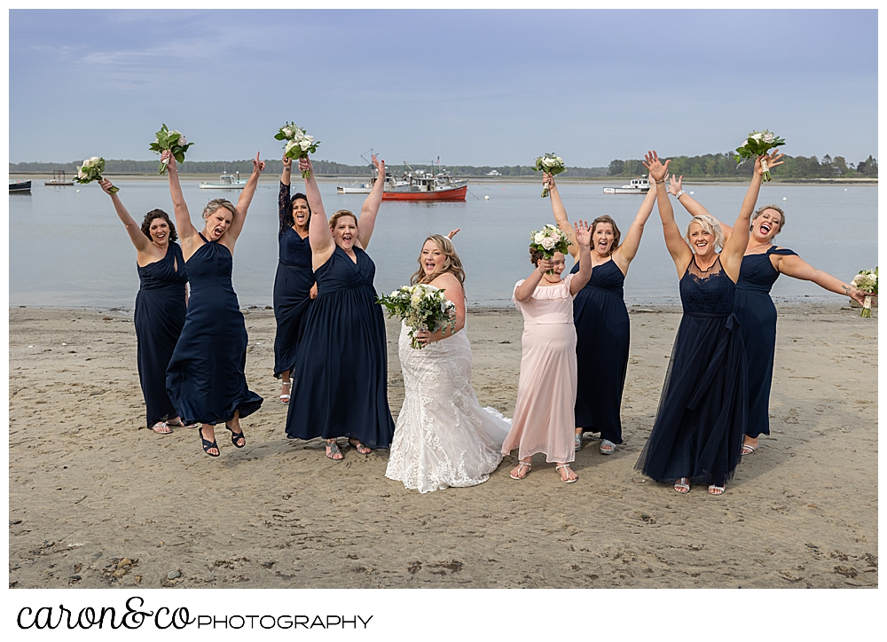 a bride in white, stands with her bridesmaids in blue, as they cheer on the beach at Pine Point Maine wedding