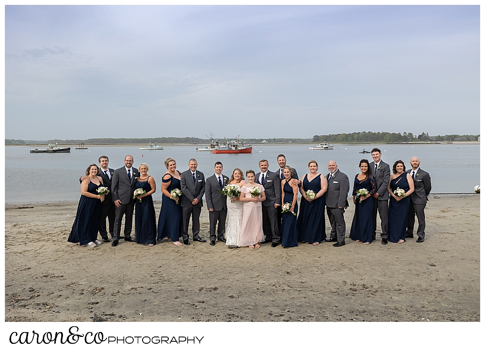 a bride and groom stand together with their bridal on the beach at Pine Point Fisherman's Coop, Pine Point, Scarborough, Maine