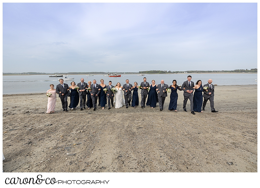 a bride and groom with their bridal party, linked arms and walking on the beach at Pine Point, Scarborough, Maine