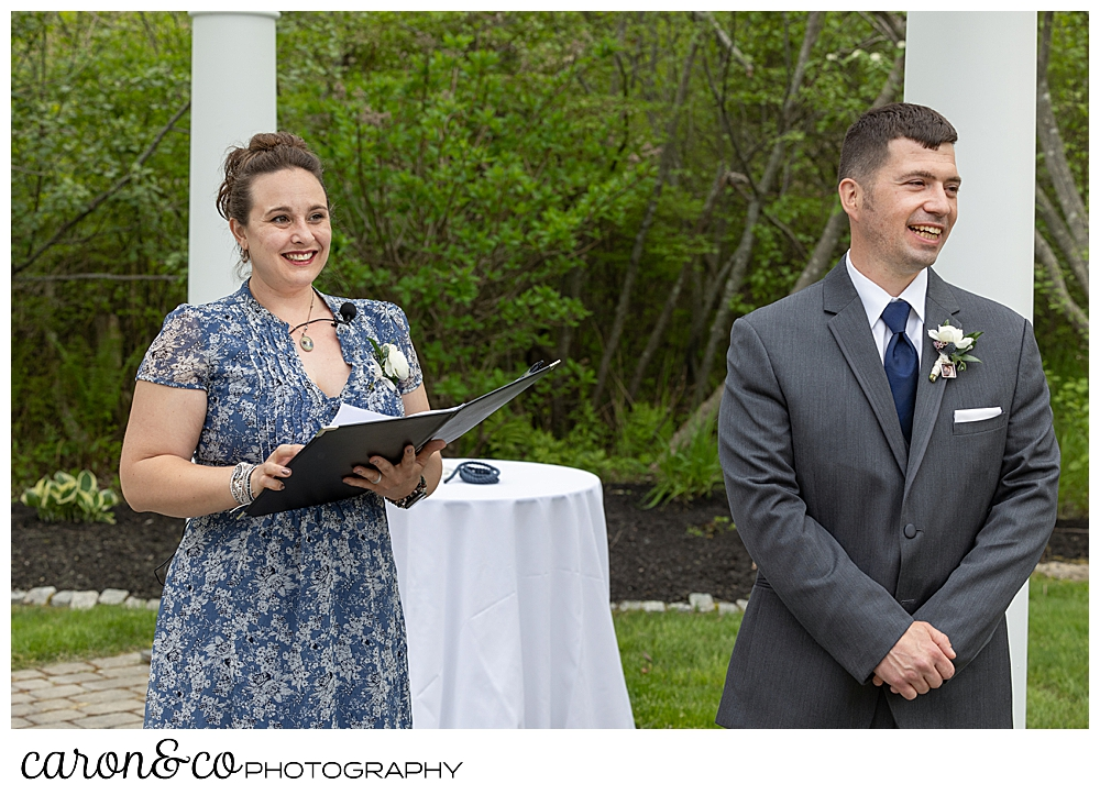 a groom and an officiant stand under the pergola awaiting the bride for a Pine Point Maine wedding ceremony