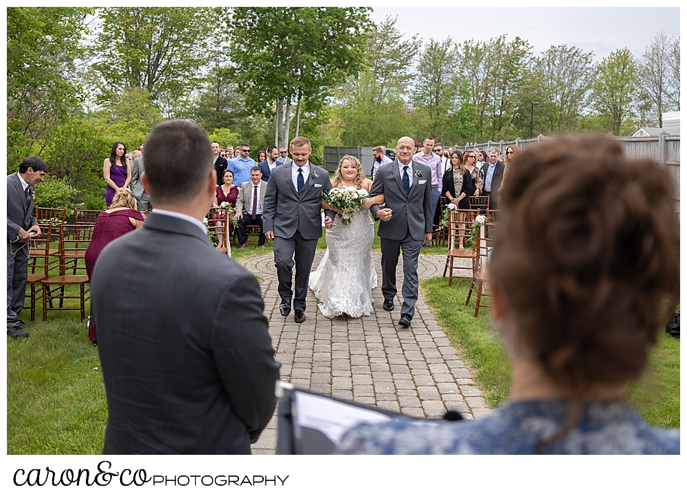 a view from behind the groom and officiant, of a bride being walked down the aisle by her uncle and brother, at a Pine Point Maine wedding