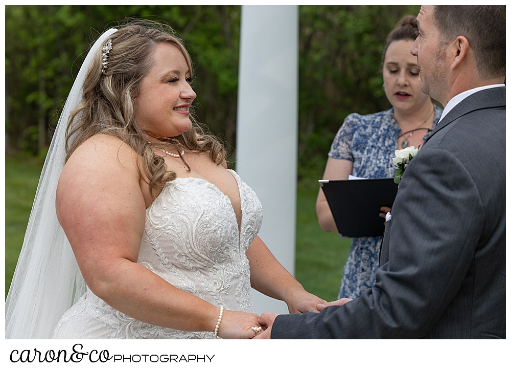 a beautiful bride smiles at her groom during their Pine Point Maine wedding ceremony