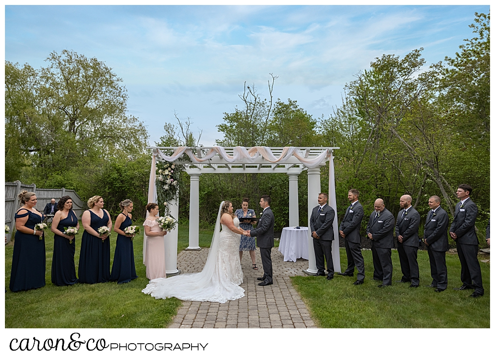 the pergola at the Landing at Pine Point, Scarborough, Maine, with a bride, groom, officiant, and wedding party