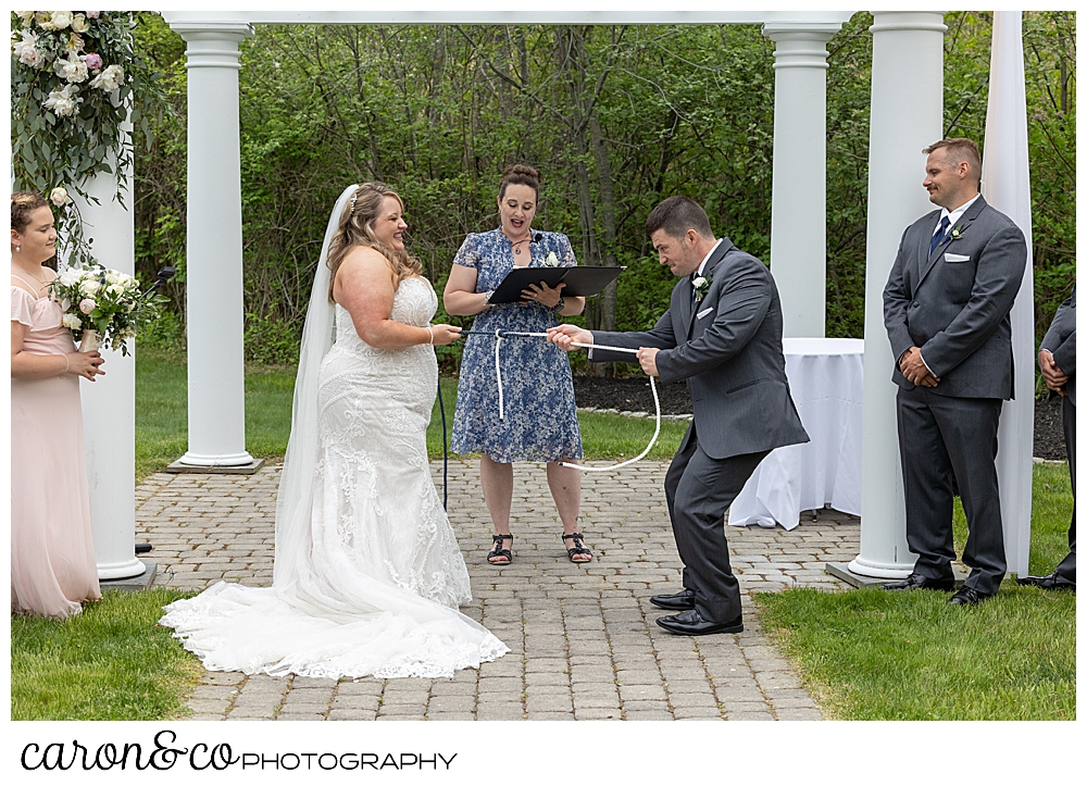 a bride and groom standing before a pergola, and their officiant, complete a knot tying ceremony, as they each pull the secure the ropes at their Pine Point Maine wedding ceremony at the Landing at Pine Point