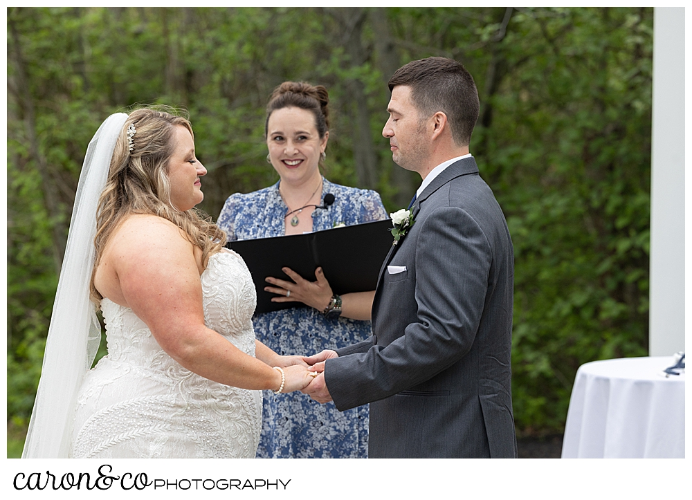 a bride and groom hold hands in front of their officiant, during their wedding ceremony outside at the Landing at Pine Point, Scarborough, Maine