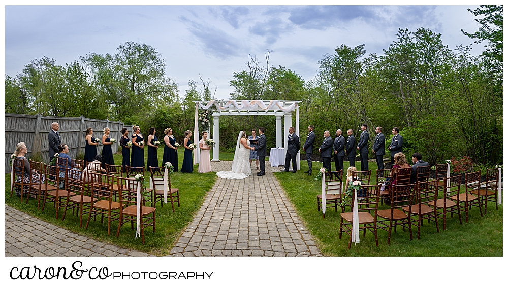 a wide view of a wedding ceremony at the Landing at Pine Point Scarborough, Maine, with the bride, groom, and officiant under the pergola, and the bridal party on either side