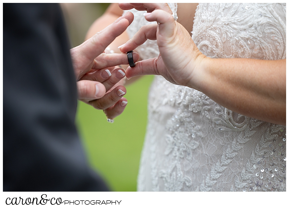 a bride putting a wedding band on the finger of her groom, at their Pine Point Maine wedding